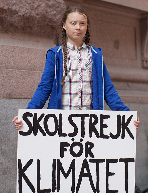 Greta Thunberg, climate activist, outside the Swedish parliament building, holds Skolstrejk för Klimatet - School strike for Climate banner
